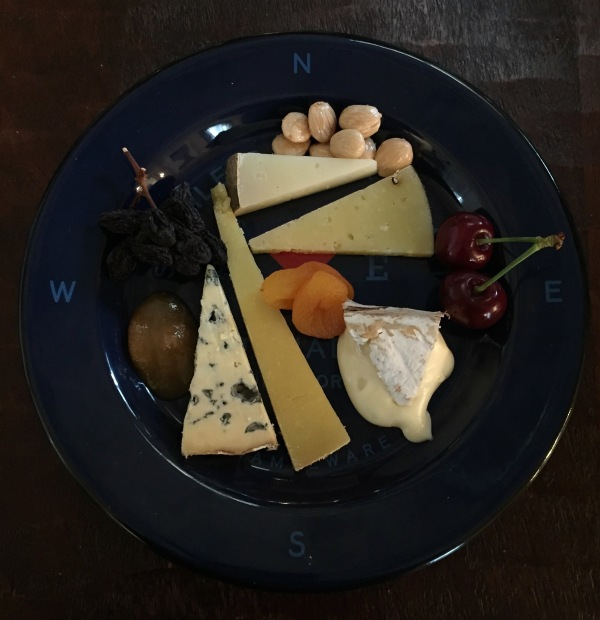 Plate with five different cheeses and a variety of fruits and nuts